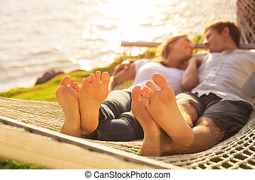 Couple relaxing in tropical hammock - Romantic couple...