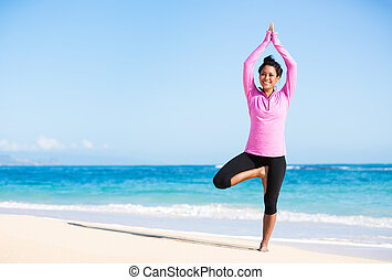 Boung woman in yoga pose at the beach - Beautiful young...