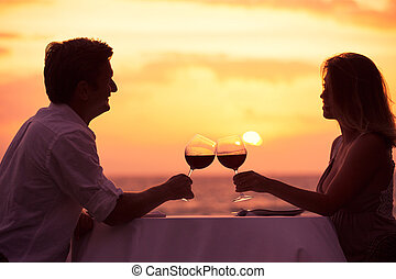 Couple enjoying romantic sunnset dinner - Couple sharing...