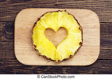 Pineapple slices with a cut in the shape of hearts on a...