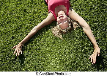 Summertime - Woman lying on grass in the sunshine