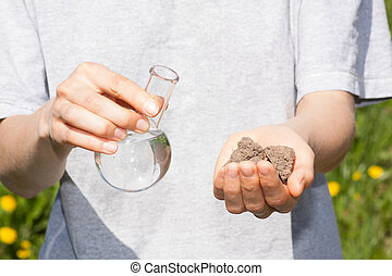 dry soil in hand and a flask with water - dry soil in female...