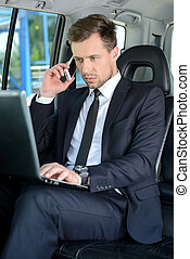 Businessman In The Car - Young successful businessman riding...