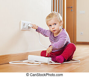 Baby playing with electrical extension and outlet at home