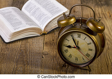 Bible with clock on wood - open Holy Bible with clock on...