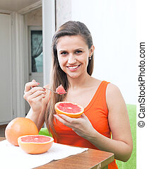 happy woman eating grapefruit