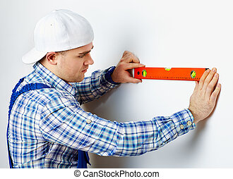 Worker using spirit level - Young construction worker using...