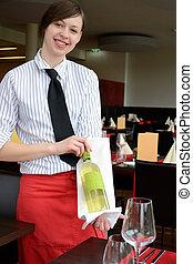 Kellnerin mit Weinflasche - Restaurantfachfrau praesentiert...