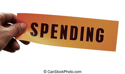 Cutting Spending Concept - Cutting a bright orange piece of...
