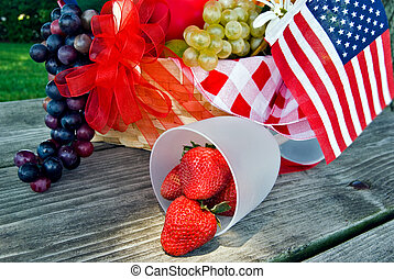 Spilled Sunshine - Patriotic fruit basket on picnic table.