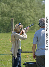 clay pigeon shooting - a lady learning to shoot at clay...