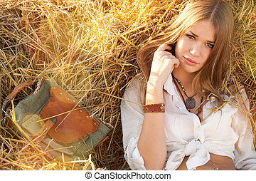 Beauty woman relaxing in the straw in field. Young woman in...