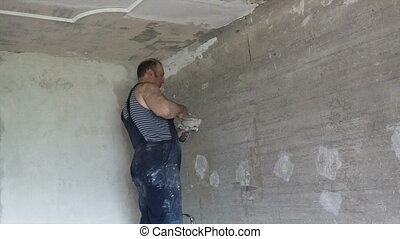 Plastering wall - Apartment renovation. The man plasters a...