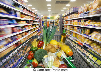 Shopping cart with foods in the supermarket - Shopping cart...