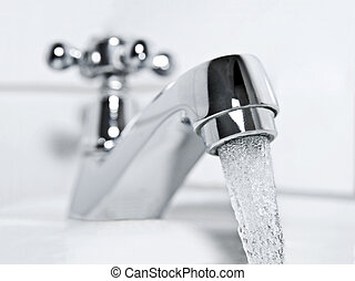 Tap and drinking water - drinking water flows from a chrome...