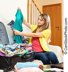 young woman sitting on a sofa near the open suitcase -...