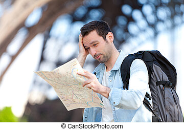 Young attractive tourist reading map in Paris, France