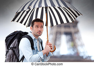 Young attractive man suffering rain in Paris - View of a...