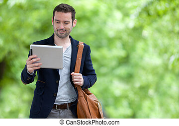 Young attractive man using tablet in Paris - View of a Young...