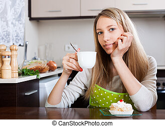 Smiling woman drinking tea with cake