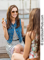 Two beautiful woman eating ice cream on a bench in the city