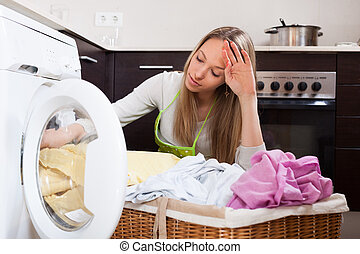 tired woman doing laundry - tired woman doing laundry with...