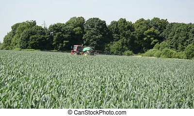 spray pesticides - tractor with long spreading spray nozzles...