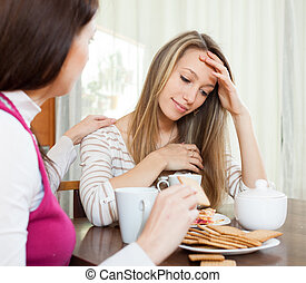 Sad woman has problem, other woman consoling her at home