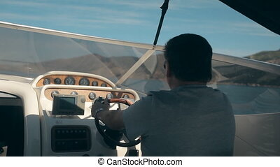 Mature man drives the yacht and looks at the sea
