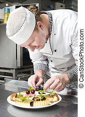 chef prepares a meal - chef preparing food in the kitchen at...