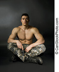 young sexy man with athletic body in camouflage with gun -...