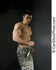 young sexy man with athletic body in camouflage with knife -...