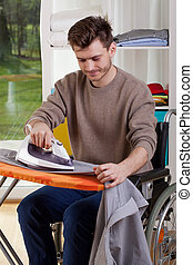 Happy disabled man during ironing shirt, vertical