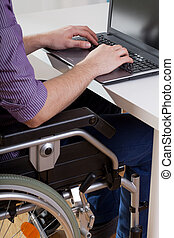 Man on wheelchair working on laptop, vertical