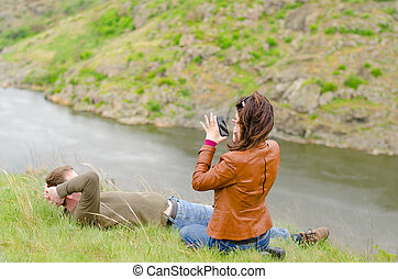 Young woman photographing a man on a cliff top - Young woman...