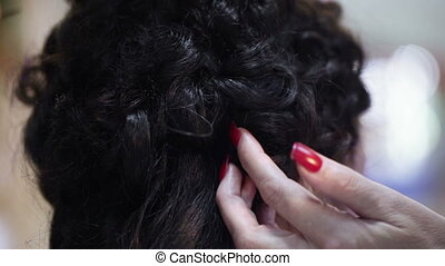 Hair styling - Hairdresser using hairpins attaches to hair...