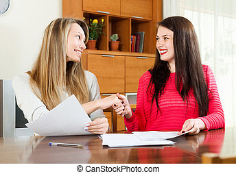 Two women works with papers at table at office