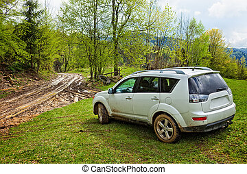 SUV in offroad - White SUV in a picturesque landscape with a...