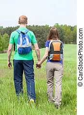 Couple holding hands and walking on a grass field - Back...