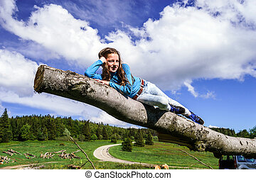 Cute teenage girl lie down on wood, nature landscape