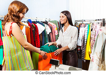 Woman with purchase after paying at cashiers desk - Happy...