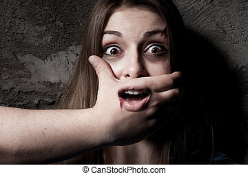 No! Terrified young woman with hand covering her mouth...