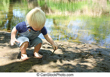 Young Child Playing in Mud by River - a young caucasian...