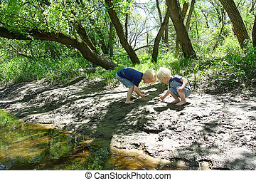 Children Playing Outside at the River - Two young children,...