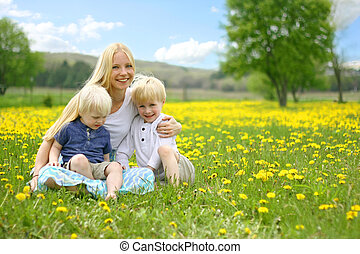 Mother and Two Children Relaxing in Flower Meadow
