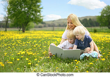 A happy young mother is sitting outside in a meadow of...