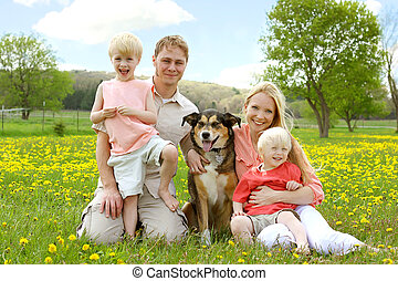 Happy Family Portrait in Flower Meadow - A happy family of...