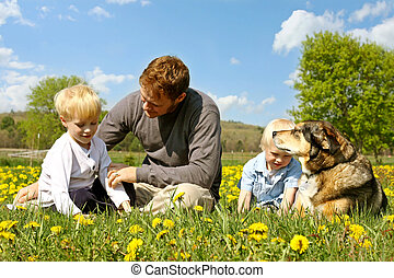 Father, Children, and Dog Relaxing in Flower Meadow - A...