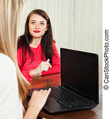 woman talking with employee with notebook - Young woman...