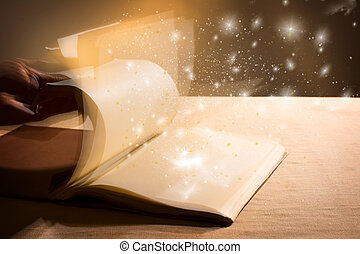 Hand leafing through a book with blank pages magic light....